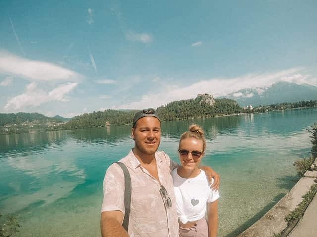 A couple taking a selfie with the castle and lake in Bled. What to do in Lake Bled