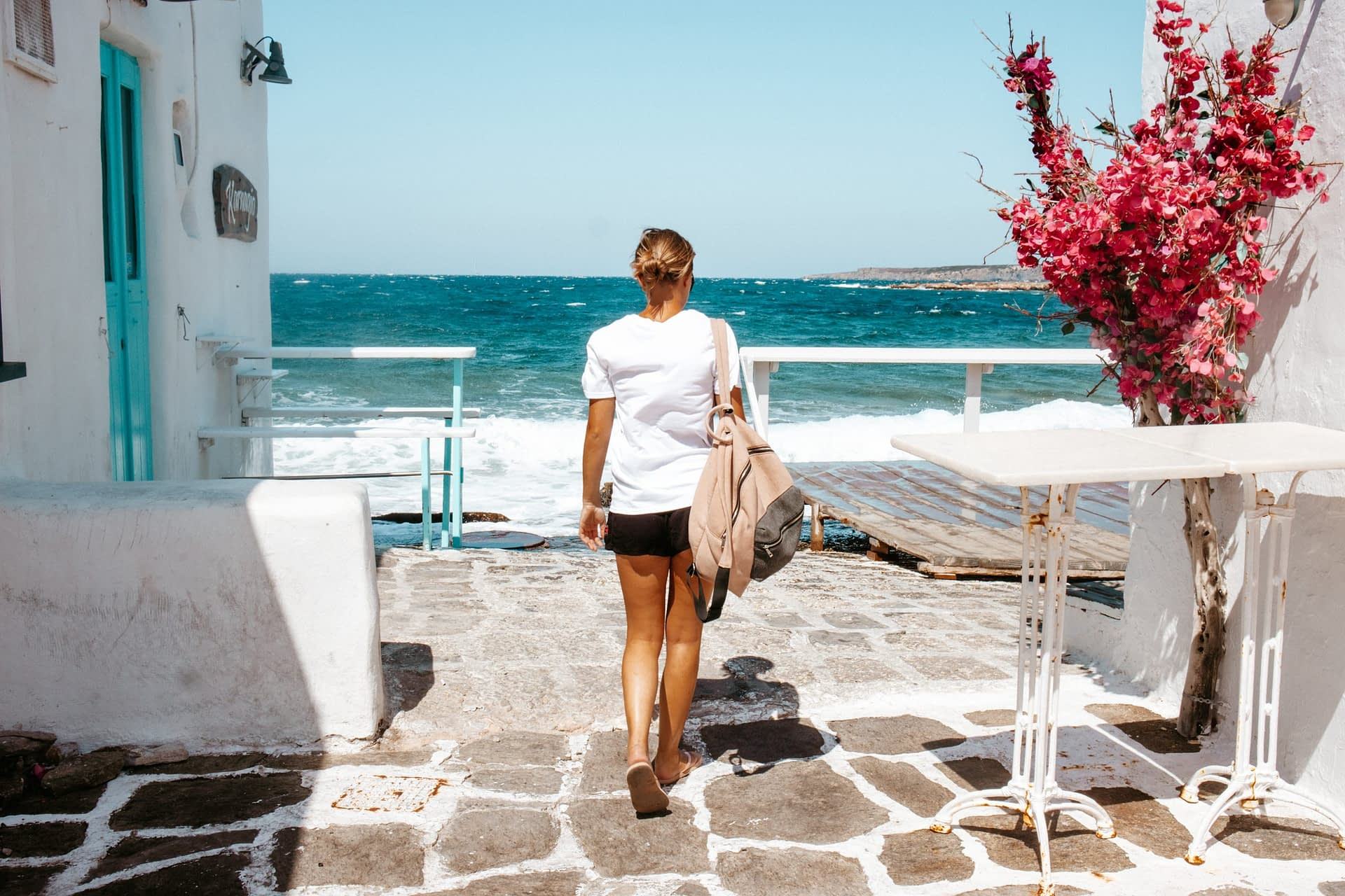 A woman walking to the sea in Naoussa. Things to do in Paros
