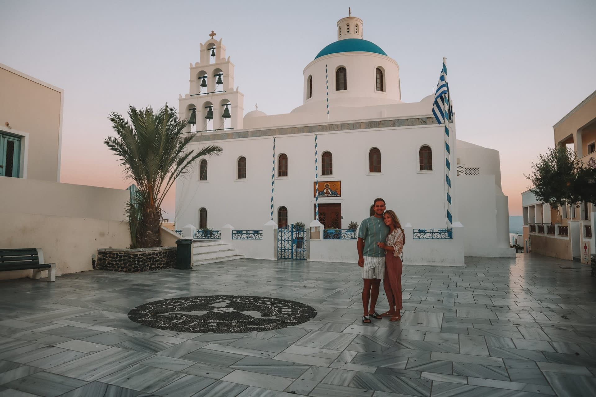 A couple stood in front of a blue domed building and bells during sunrise. Things to do in Santorini