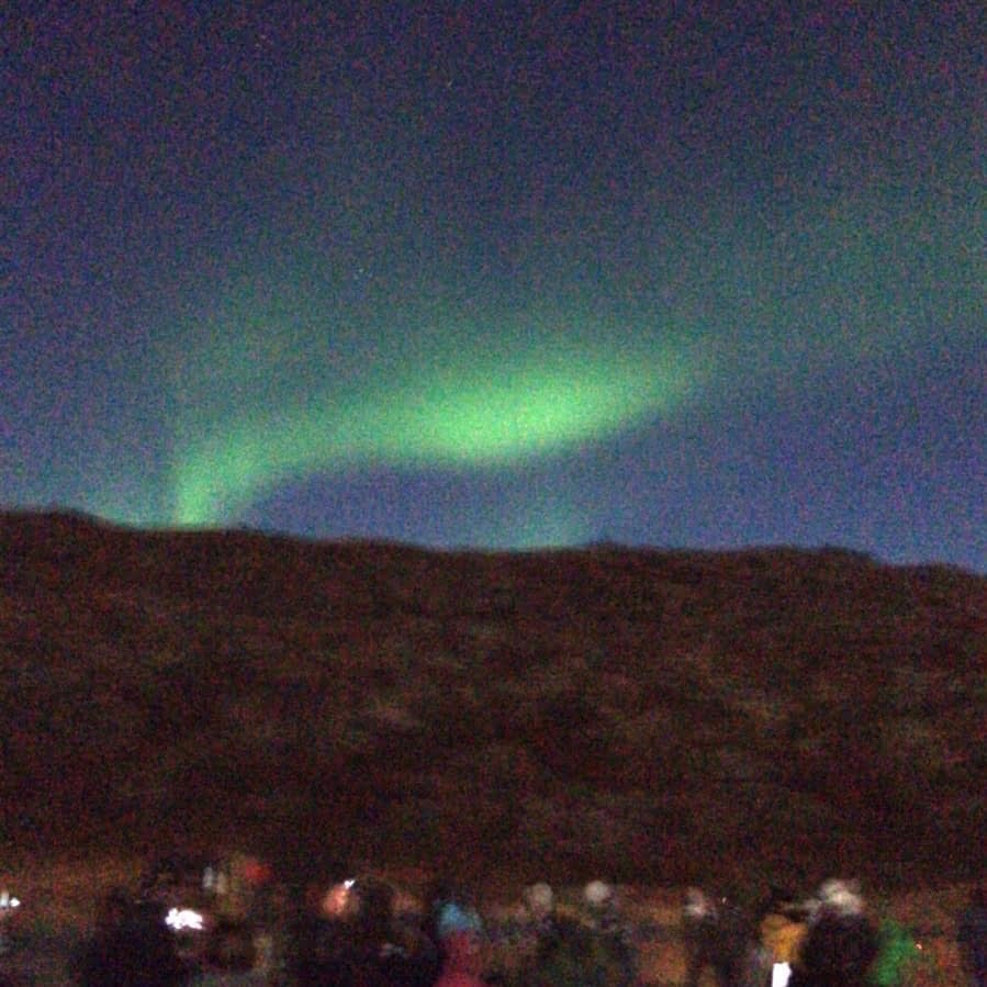 The northern lights visible in the night sky as part of the things to do in Iceland.