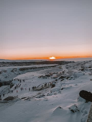 Behind Gullfoss waterfall the sun is setting. Things to do in Iceland