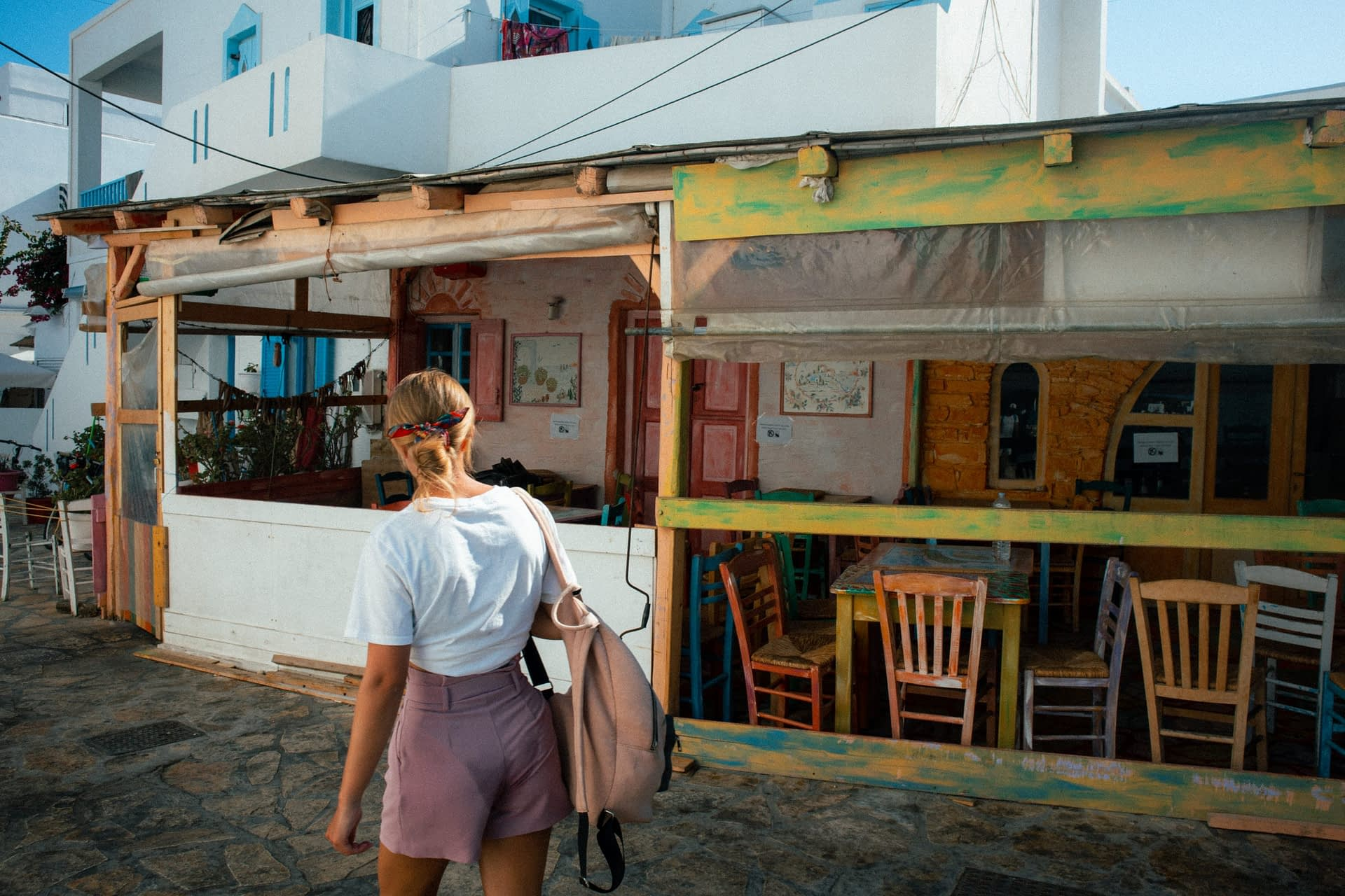 A woman strolling past colourful buildings in Antiparos. Things to do in Antiparos