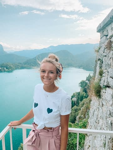A woman smiling at the top of Bled castle. What to do at Lake Bled