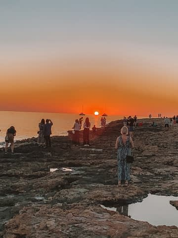 Sunsetting in the ocean with some boats and a rocky beach. Things to do in Ibiza on a budget
