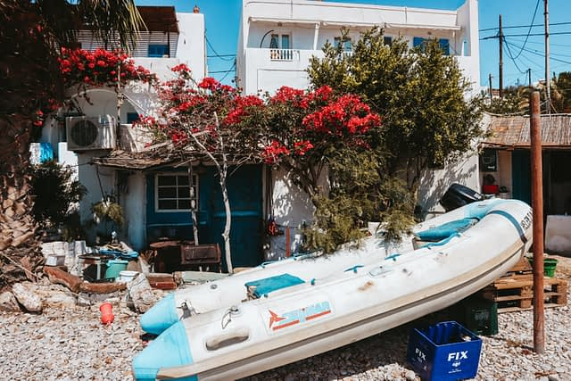 A boat on the beach with flowers blossoming around it. Where to go in Folegandros